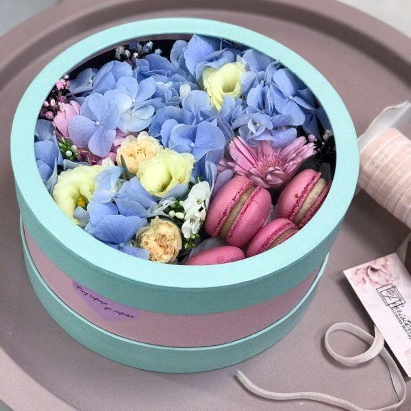 Композиція у круглій коробці з міксу квітів та макарунів